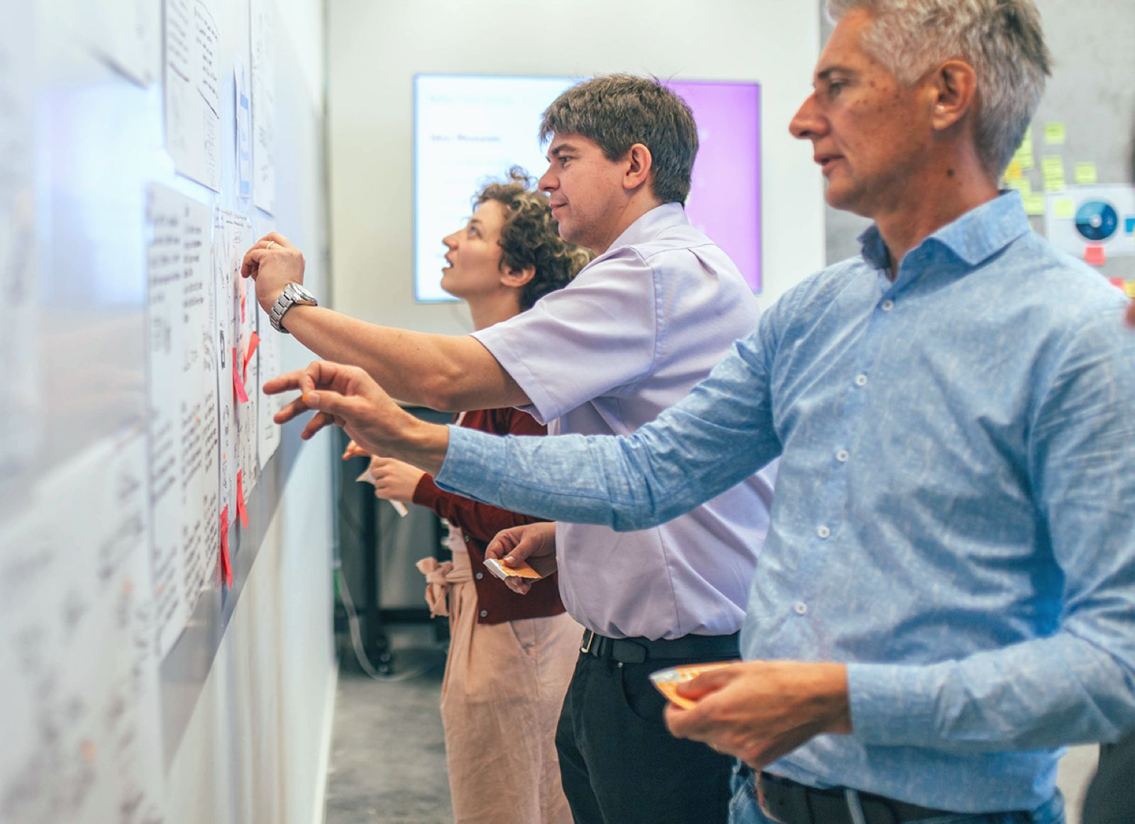 3 people working together in a strategic workshop.