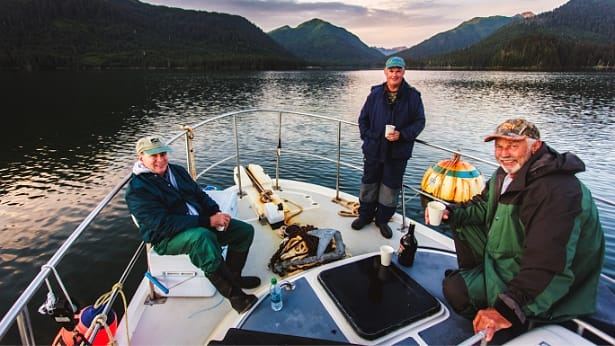 Group of three older men sitting on bow of charter fishing boat near Homer, Alaska