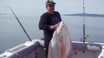 Man holding nice halibut aboard DeepStrike Sportfishing in Homer, Alaska