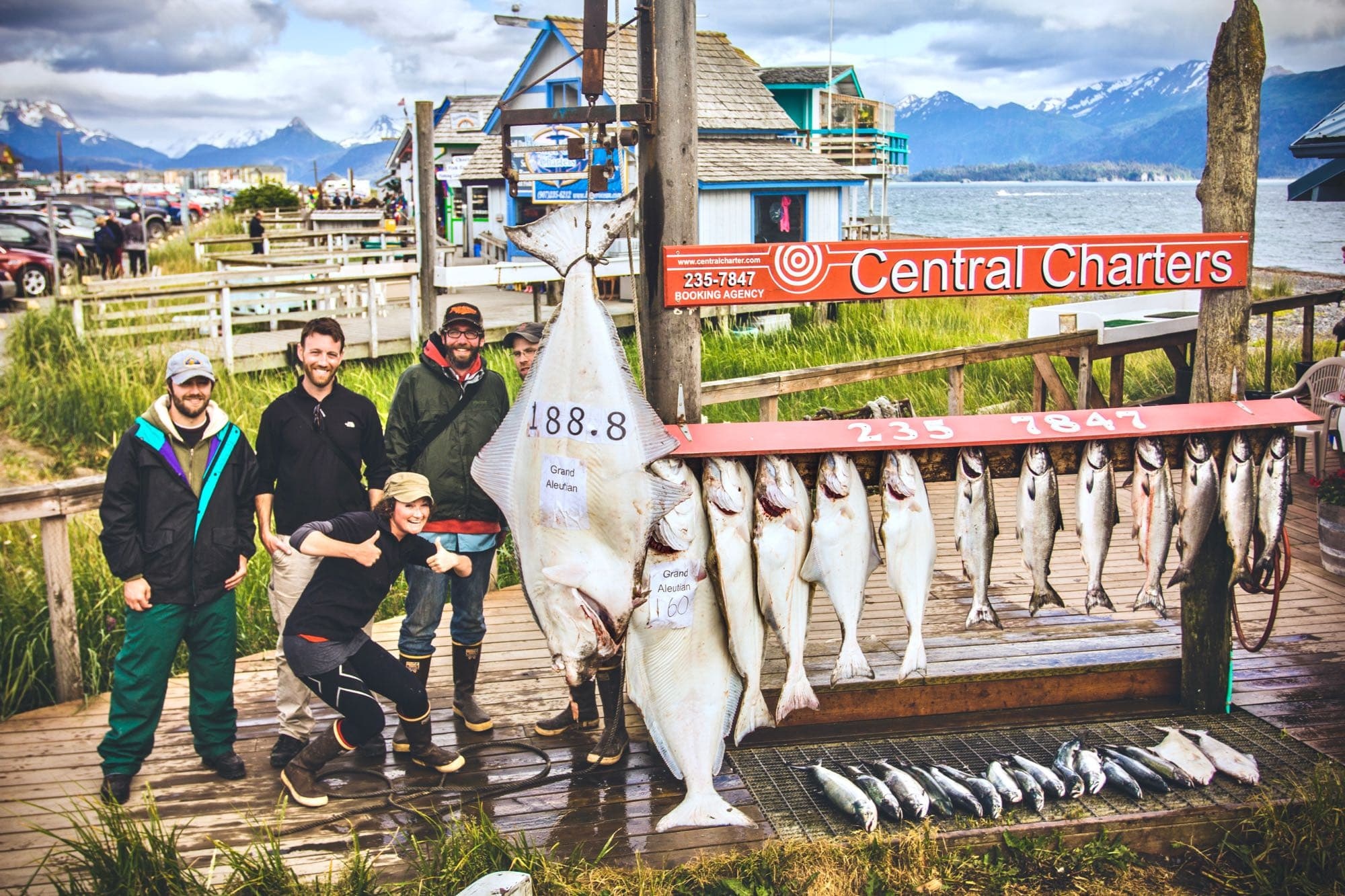 group of fishermen standing next to racked catch of halibut and salmon with deepstrike sportfishing in homer alaska