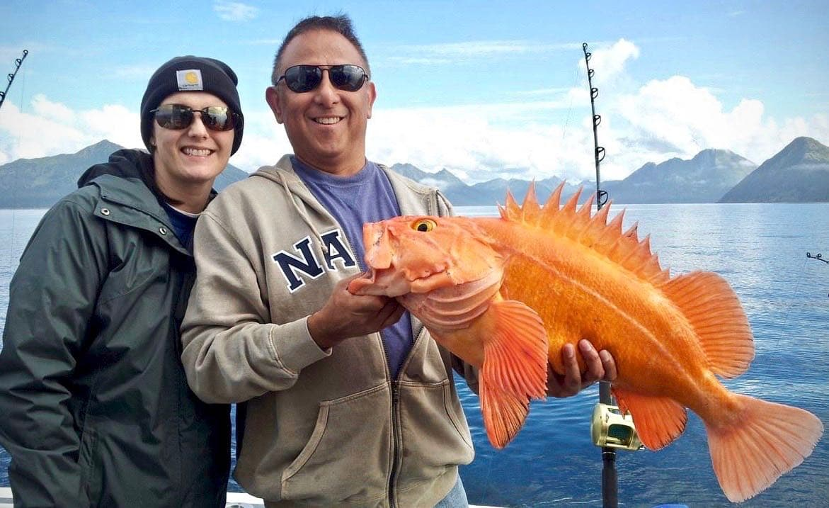 man and woman holding bright orange yelloweye rockfish charter fishing homer alaska