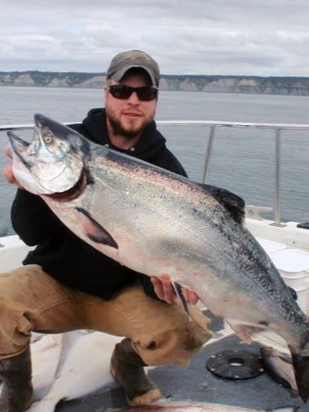 Charter fishing captain Cory Loos holding a nice salmon with DeepStrike Sportfishing in Homer, Alaska