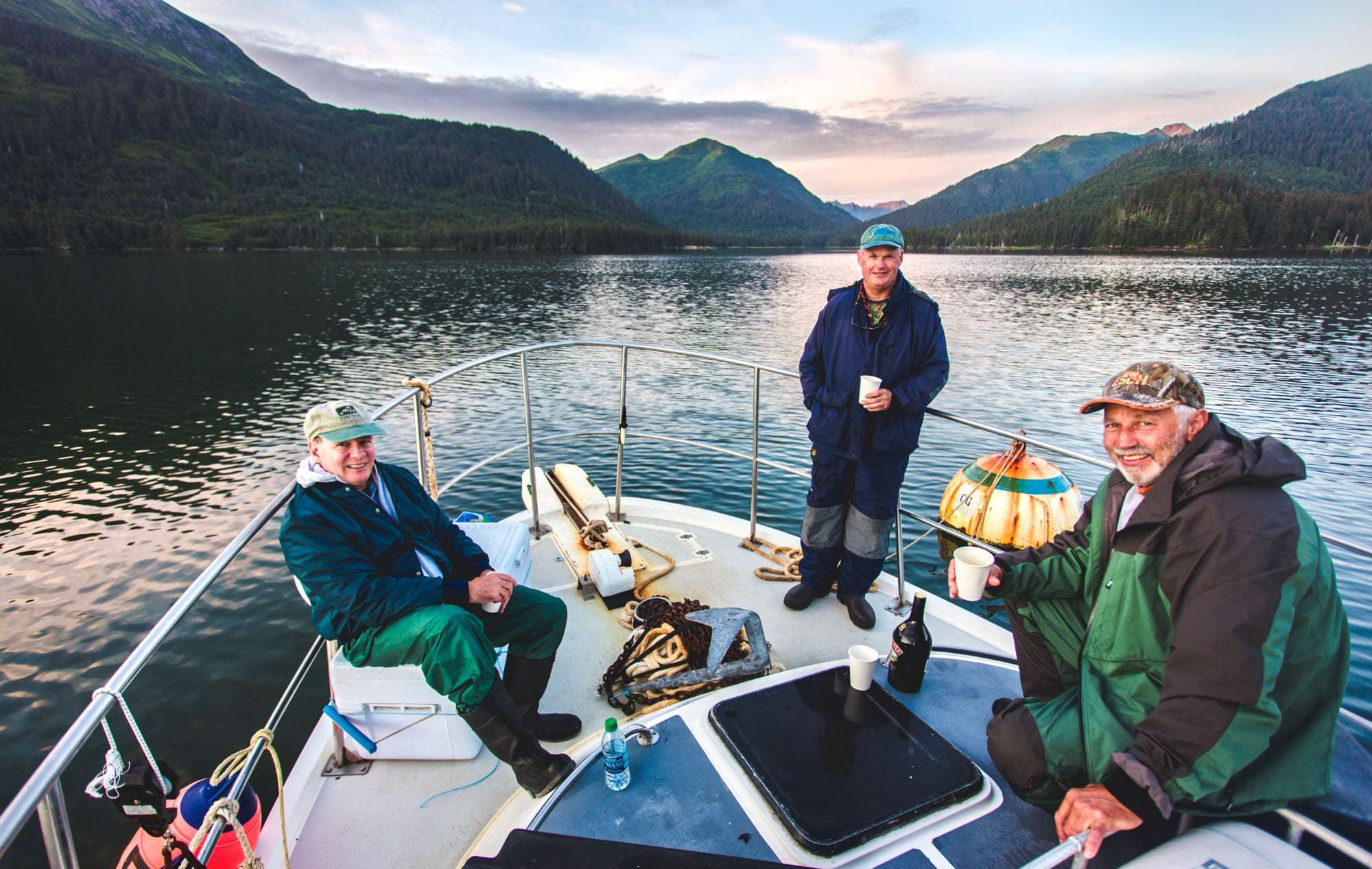 A group of older men relaxing on the bow of their overnight fishing charter boat with DeepStrike Sportfishing out of Homer, Alaska