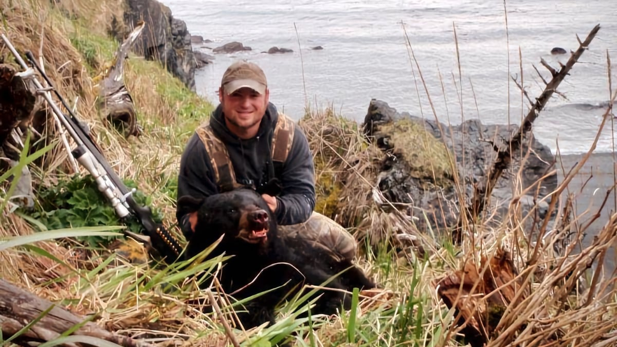Alaska black bear hunter posing with his harvest on a rocky beach. Book a black bear hunting trip with Deepstrike Sportfishing.