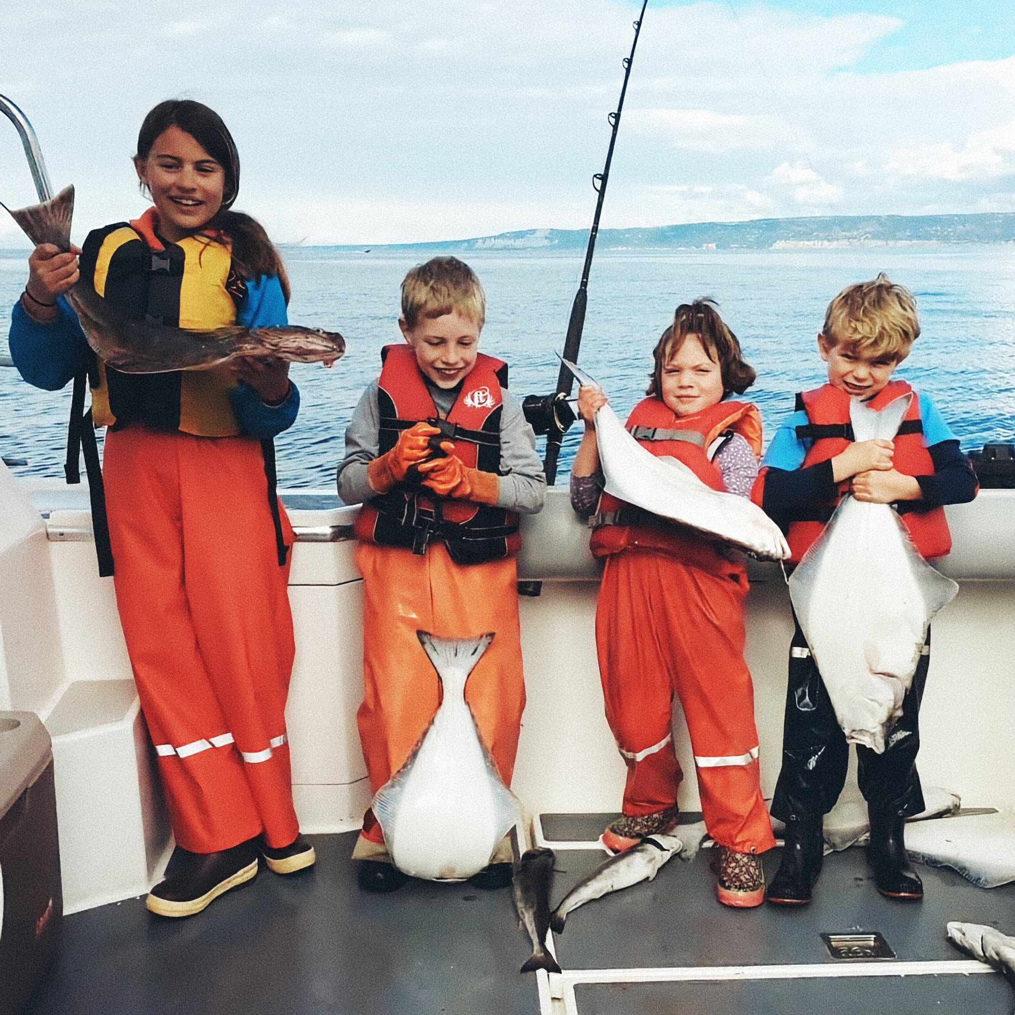 Kids holding up their charter fishing halibut catch aboard Deepstrike Sportfishing promoting the F3 program 5% for Food and Fishing