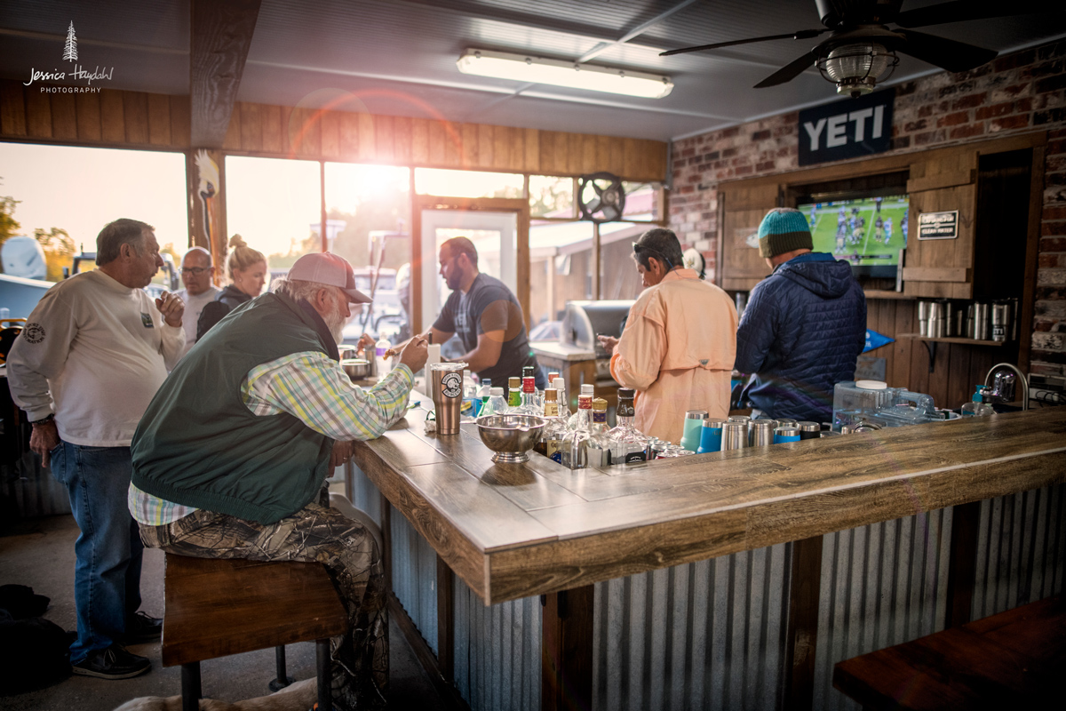 Image of clients enjoying drinks at the bar on screened in back porch.
