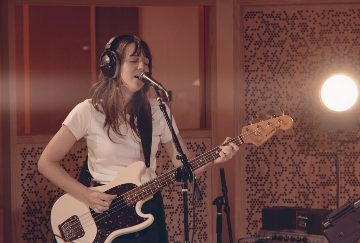 rose vastola of the band uv tv playing bass and singing during a live performance for a music video in recording studio a
