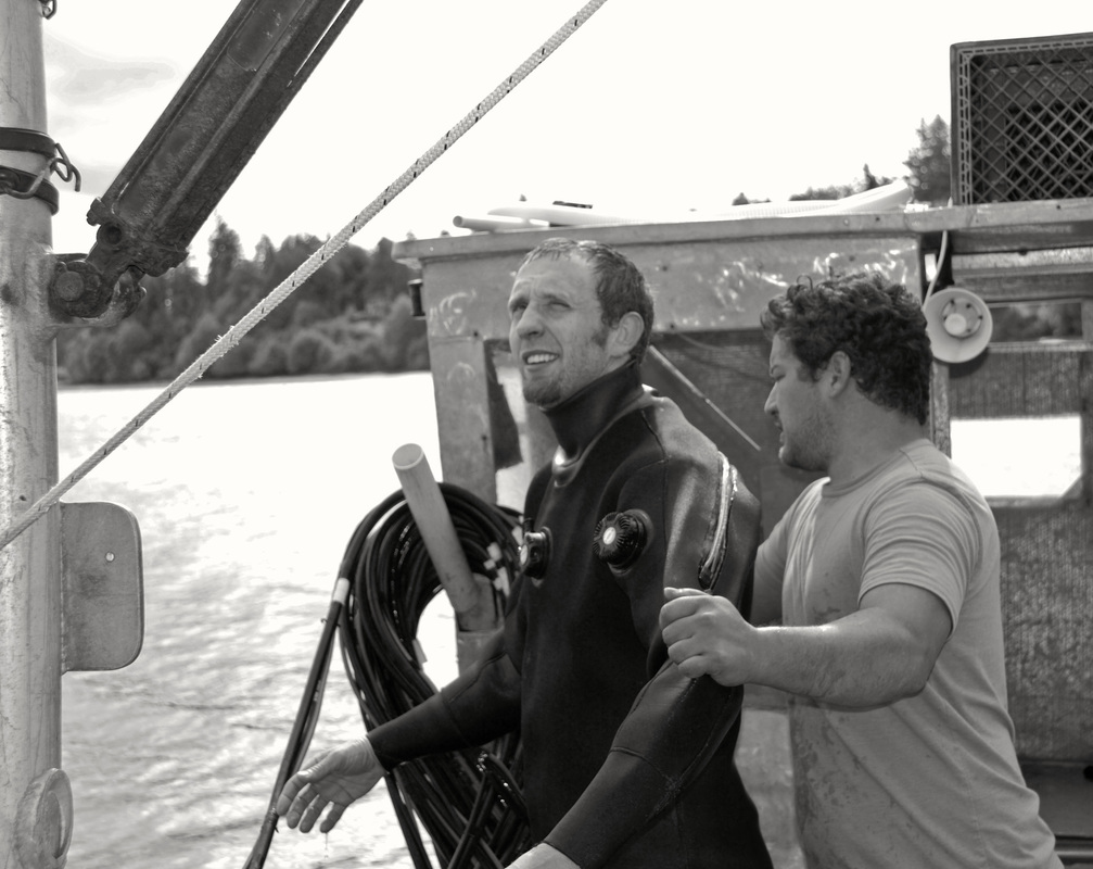 chris helping man in wetsuit gear up for dive