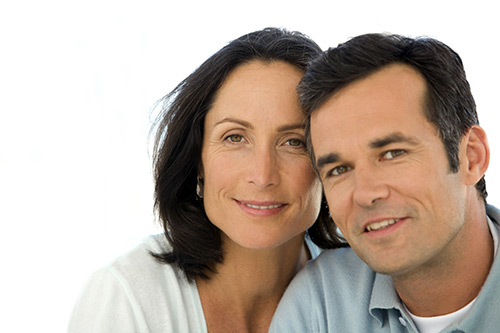 Middle aged man and woman smiling at camera