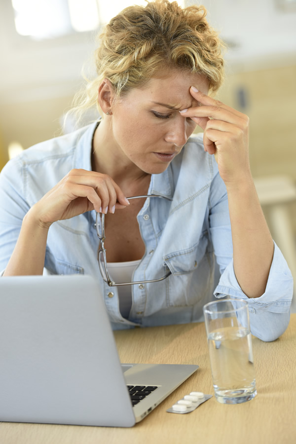 woman is working at her desk congested with a sinus infection