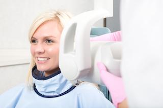 A woman smiles while getting dental x-rays | Invisible Braces Dee Why NSW