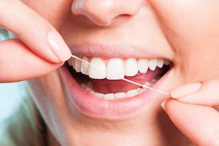 A woman flosses her teeth | Preventative Dentistry Dee Why NSW