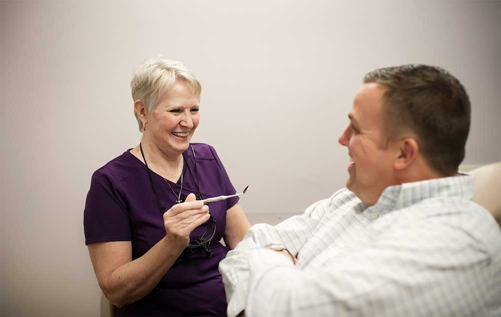 Photo of a team member talking with a male patient