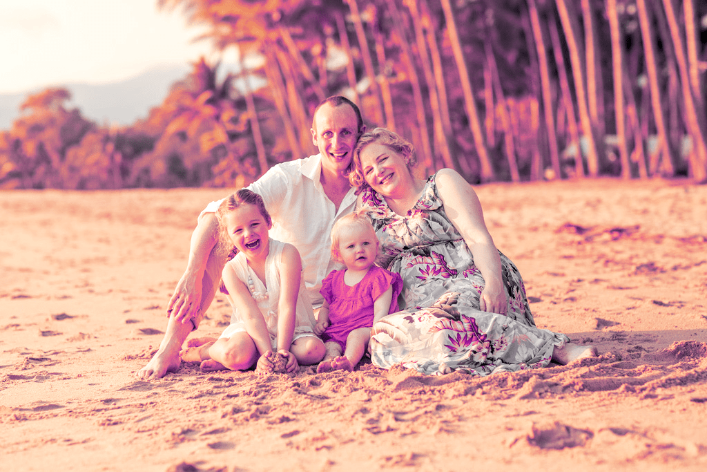 Photo of Amanda sitting on a beach with her family