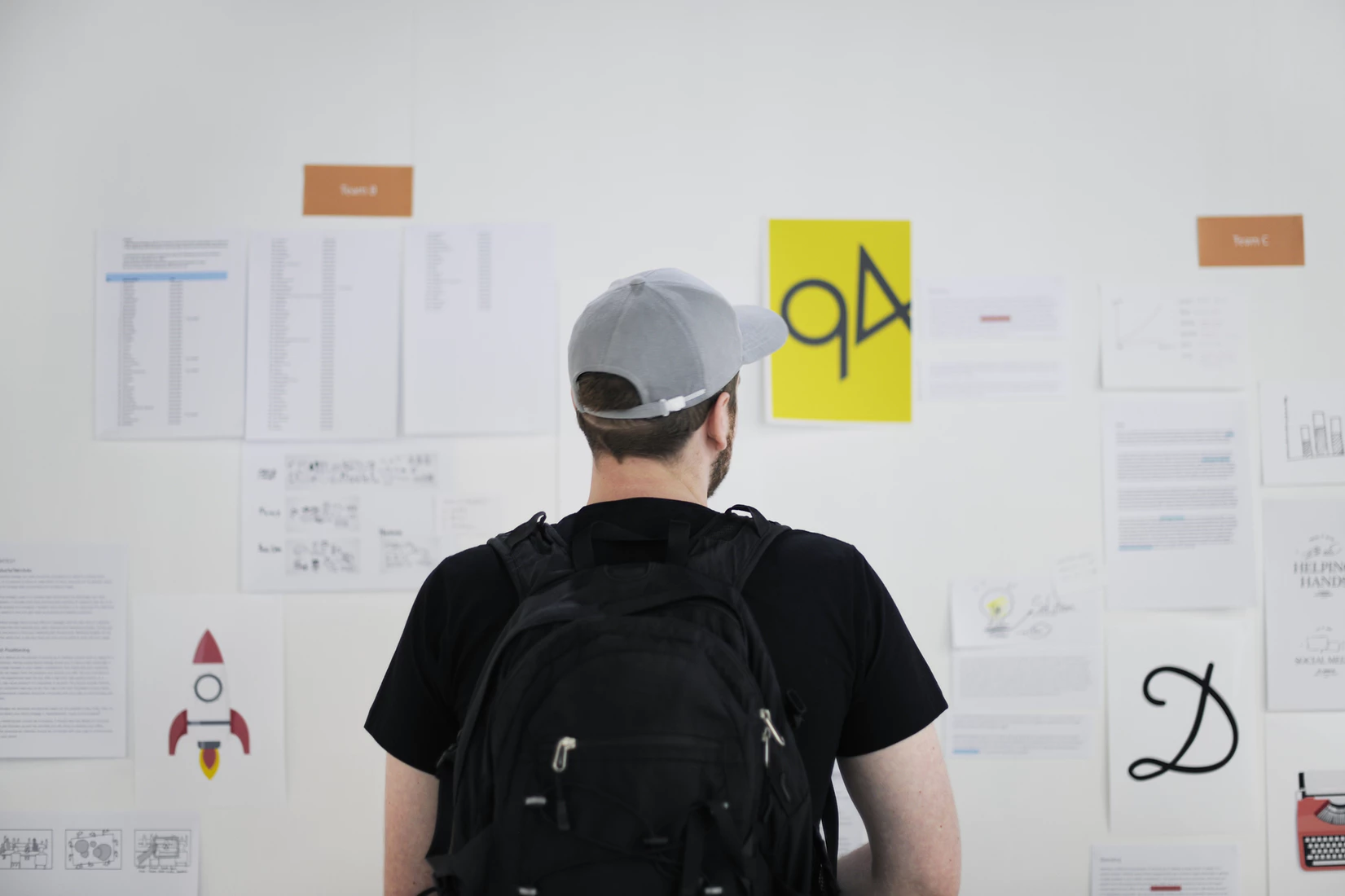 A product manager looking over project details that are mapped out on a whiteboard.