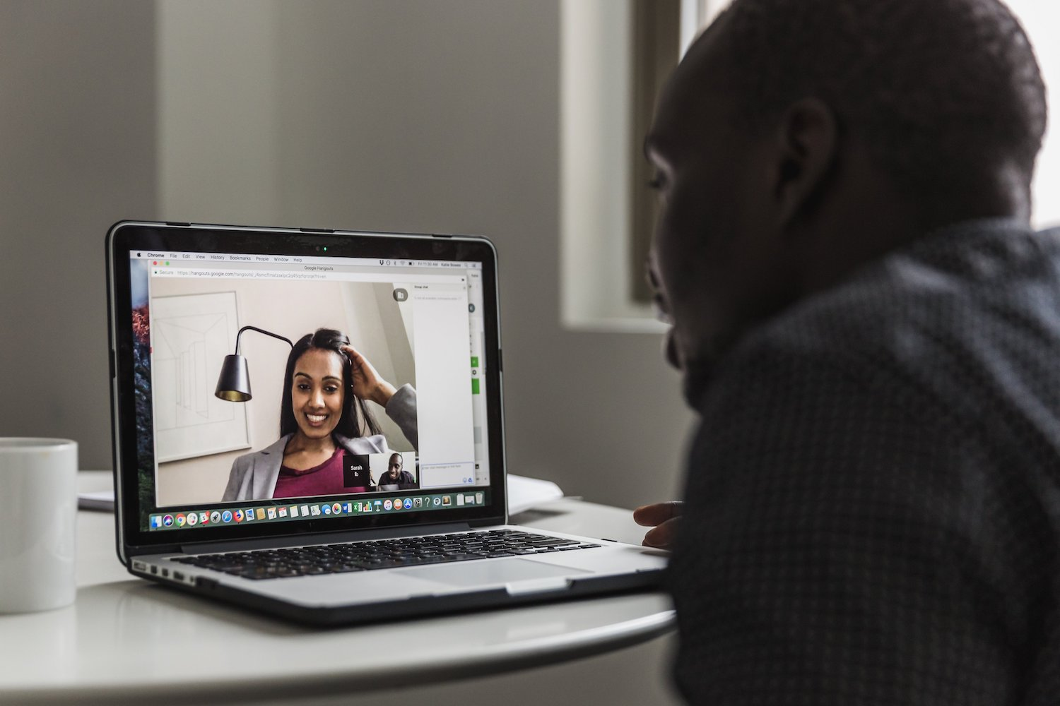 This is an image of a video conference call chat. A woman in a blazer is seen smiling on the screen while a man is talking into his computer microphone. This is a visualization of the human element in customer support.