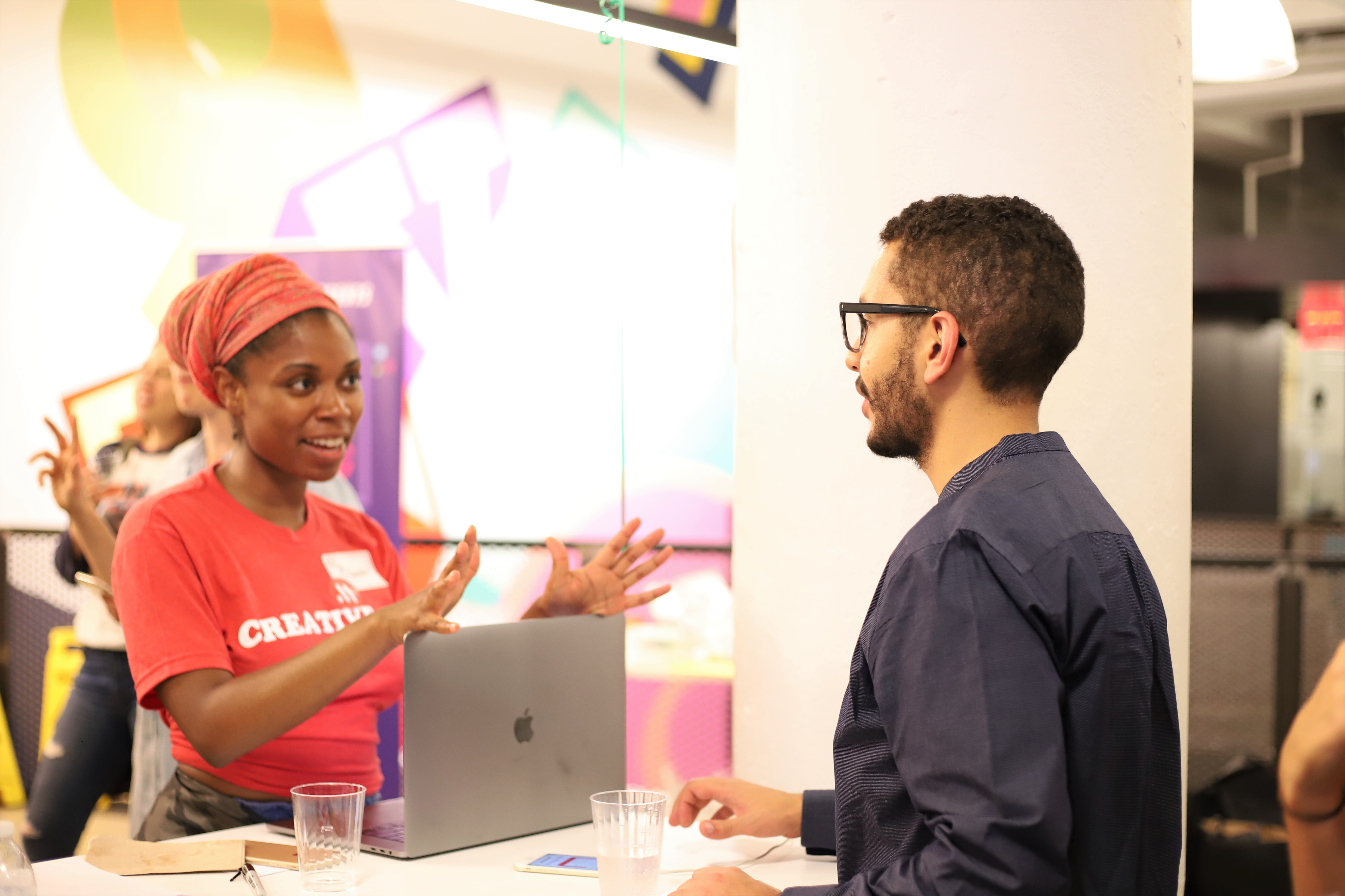 This is an event photo of a user testing event. This image shows a woman talking to a man about UX. This image features women and people of color in tech at a user testing event.