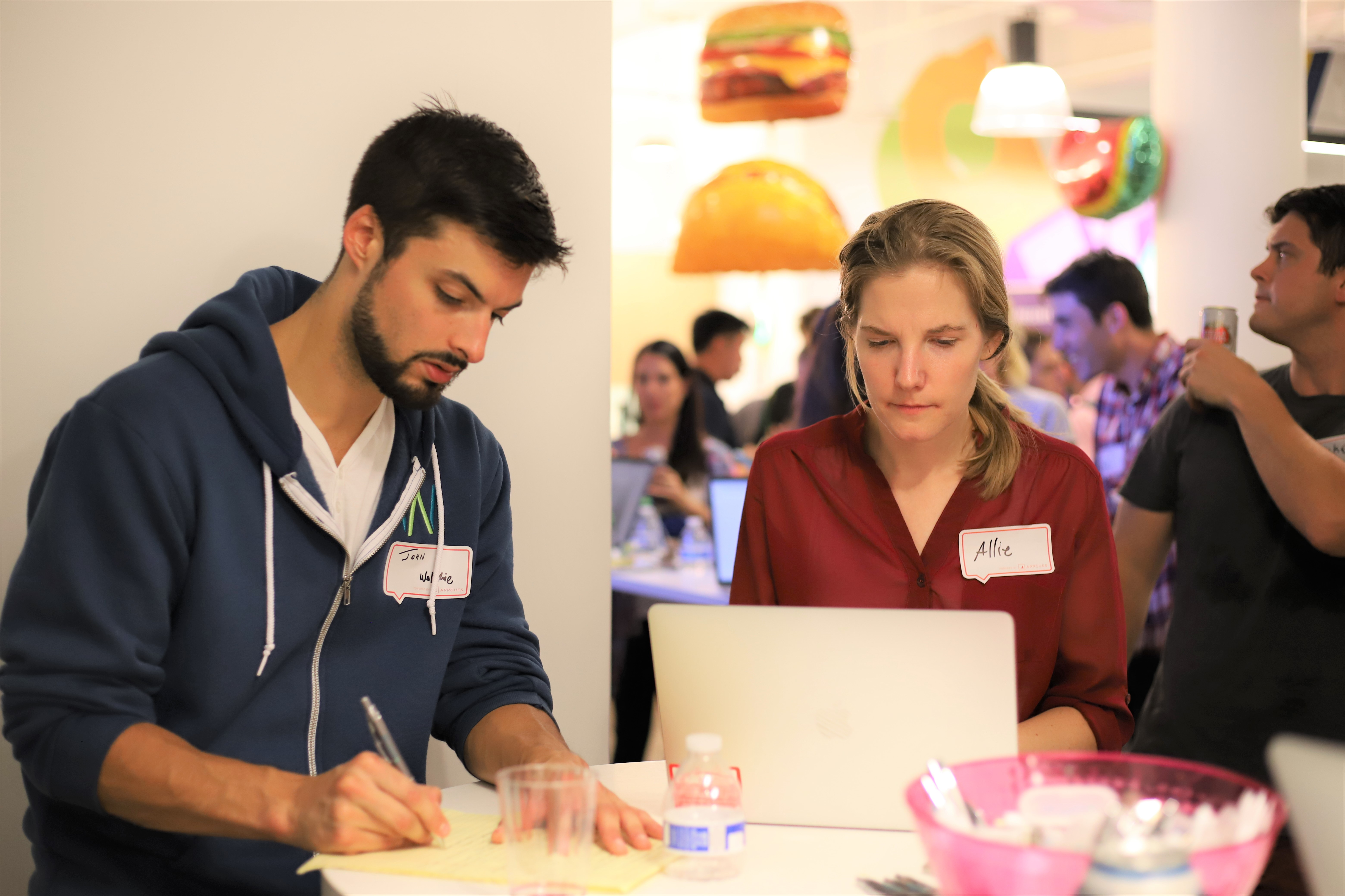 This is a picture of two users testing a product at a user testing event. This is a photo of a man and a woman wearing nametags and writing feedback about a software product that they are testing live.