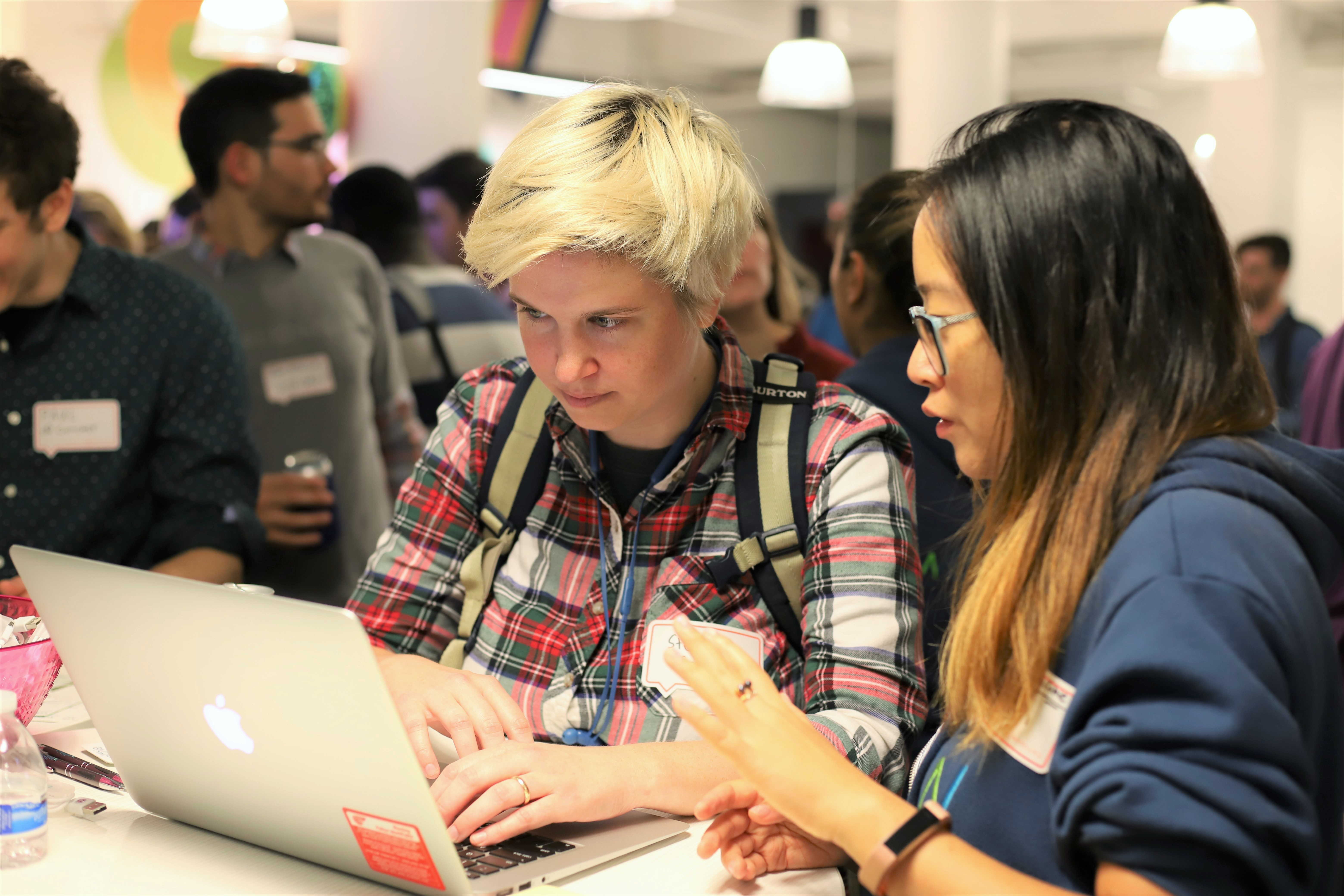 This photo shows a woman with short blonde hair testing softwareat a user testing event while she talks to a woman with dark hair who is explaining the product.