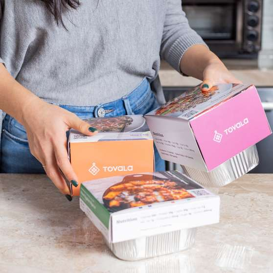 A woman with three packaged Tovala Meals on a counter top.