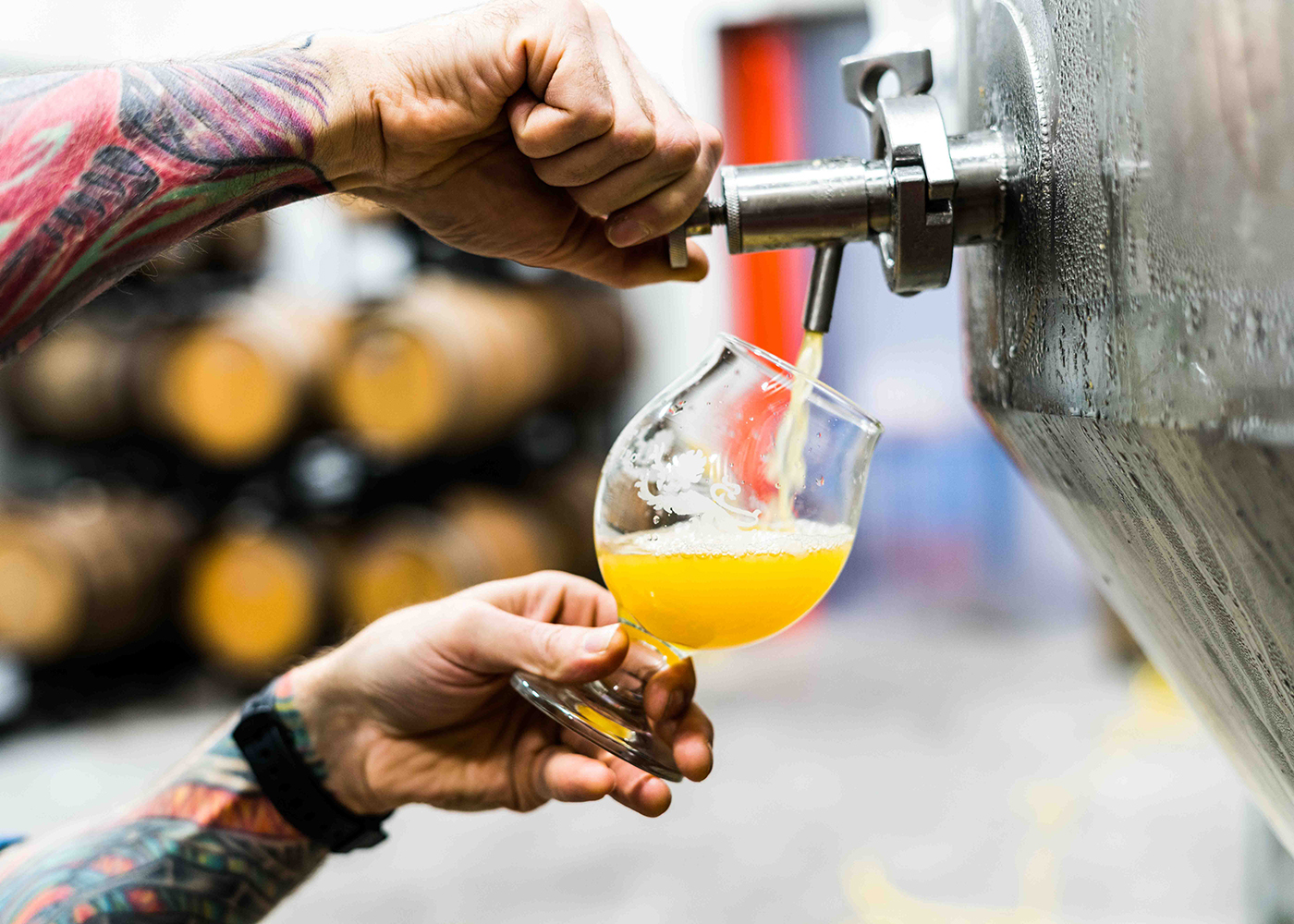 Tattooed man pouring craft beer from vat