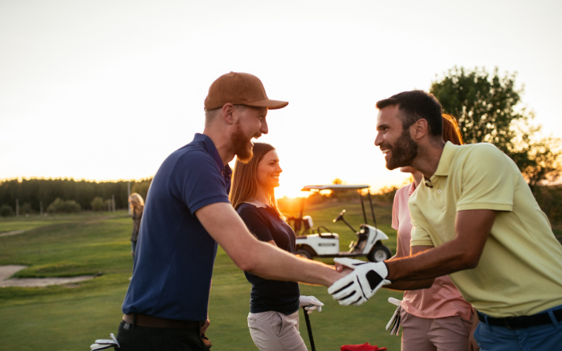 golfers shaking hands on golf course