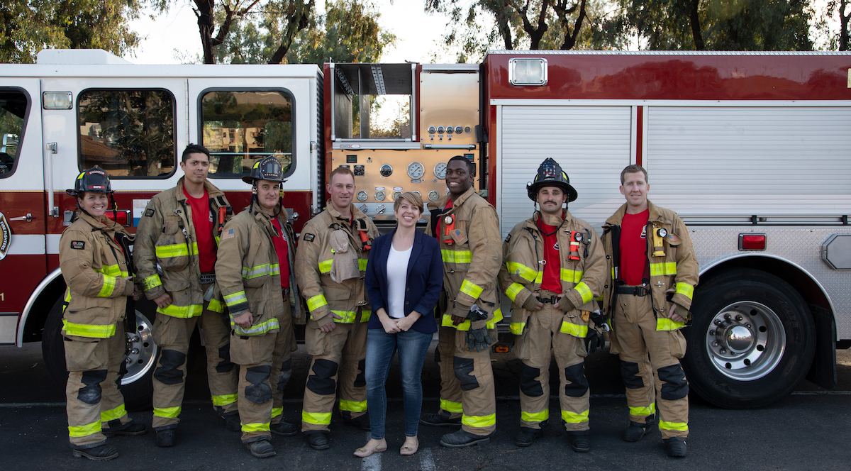 Marni von Wilpert and firefighters standing in front of a fire truck