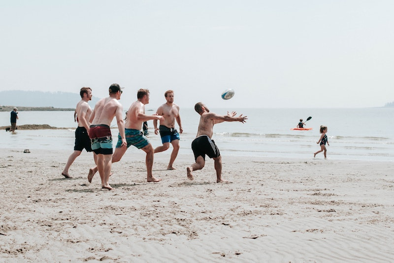 A group of men playing on the beach.