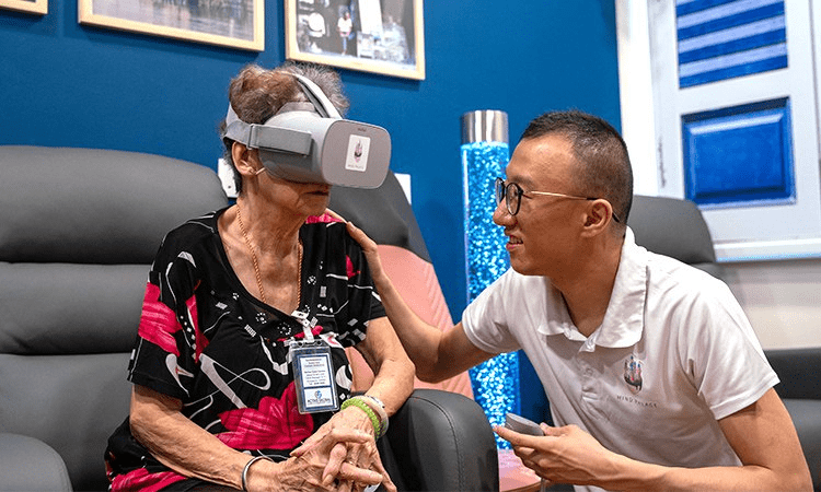 Mind Palace's founder Eugene Soh accompanying a nursing home resident in her VR experience
