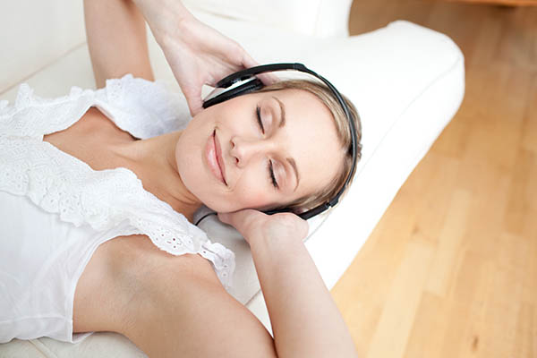 woman laying down listening to music