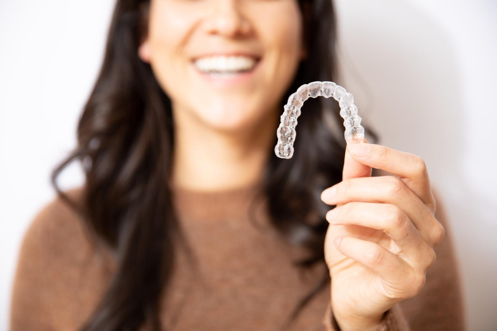 Woman holding up invisalign