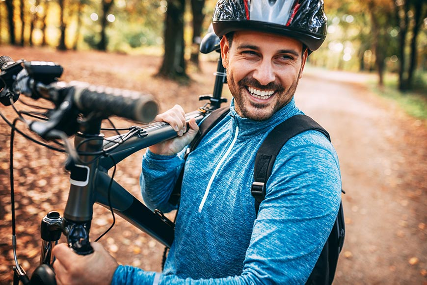 Happy member riding a bike in Littleton smiling about at-cost pricing