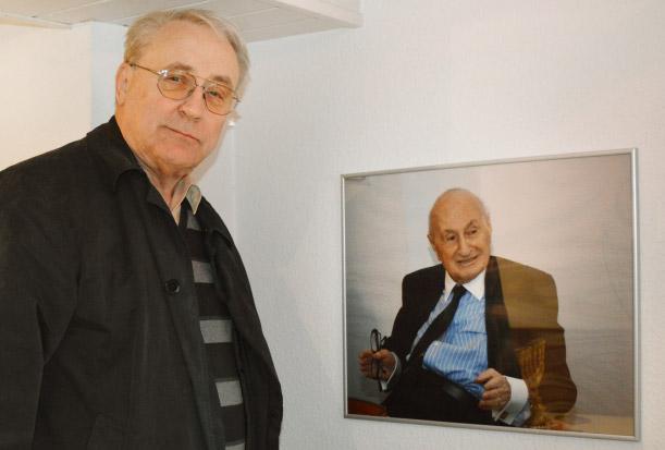 Pfarrer Dr. Wolfgang Stingl neben einem Bild von Fred Strauß