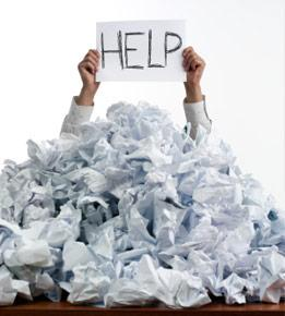 man holding up help sign under pile of paper