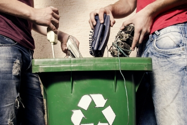 Men throwing electronics to the recycle bin