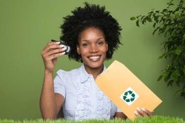 Woman putting a cell phone in a recycling bag