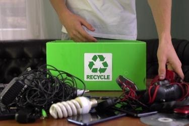 A man placing electronics inside a recycling box.