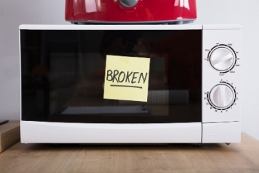 "Microwave and a  sticky note with the word ""Broken"""