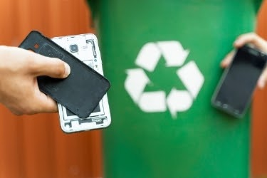 Recycling mobile phones in a green bin