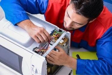 Man repairing a microwave