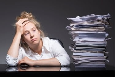 Stressed woman next to a pile of documents