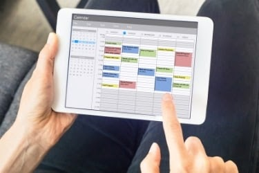 Person scheduling their time in a tablet