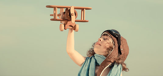 Kind mit Modell-Flugzeug aus Holz