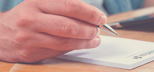 Hand mit Kugelschreiber und Notizblock
