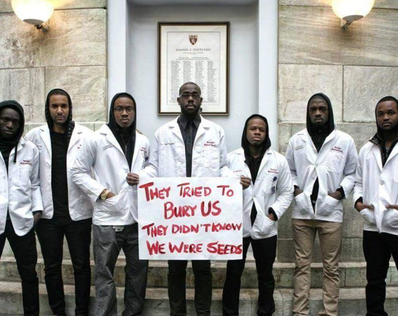 Group of Black medical students holding a sign that reads, They tried to bury us. They didn't know we were seeds.