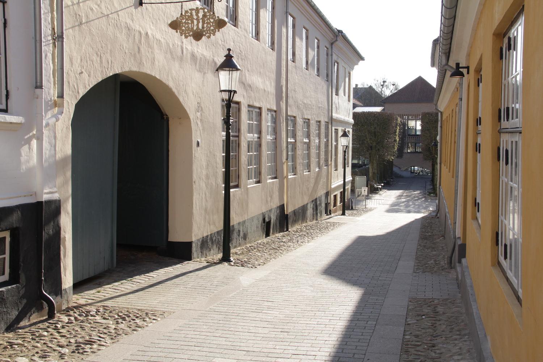 På billedet ses den nye jævne belægning samt de toppede gamle brosten der er bevaret langs facaderne