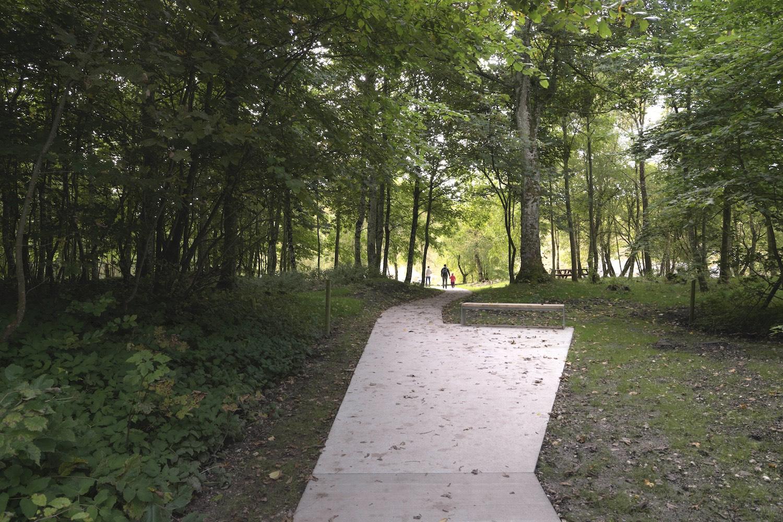 På billedet ser vi, hvordan der overalt i landskabet er opsat bænke langs med den brede betonsti, hvor man kan få et hvil eller nyde naturen.