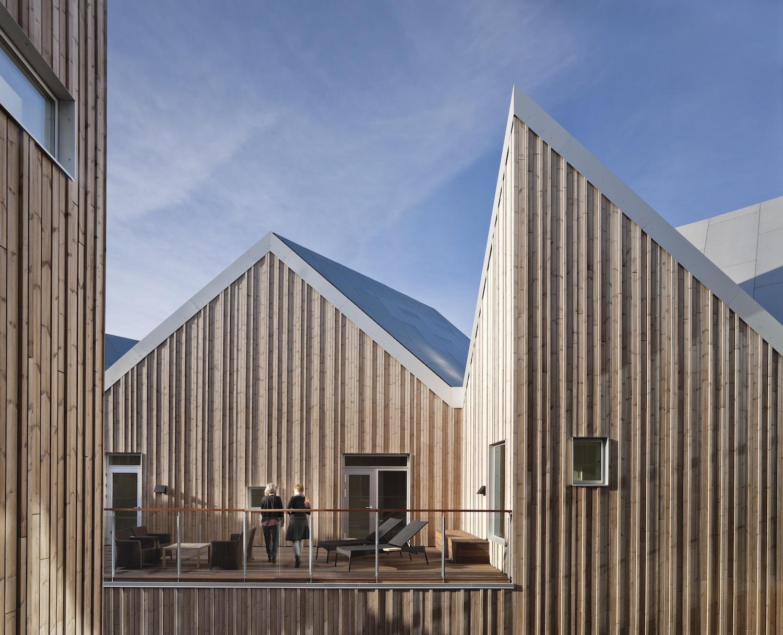 På billedet ses et hævet og mere isoleret udendørsareal, der omringet af bygningens træbeklædning skaber en varm stemning