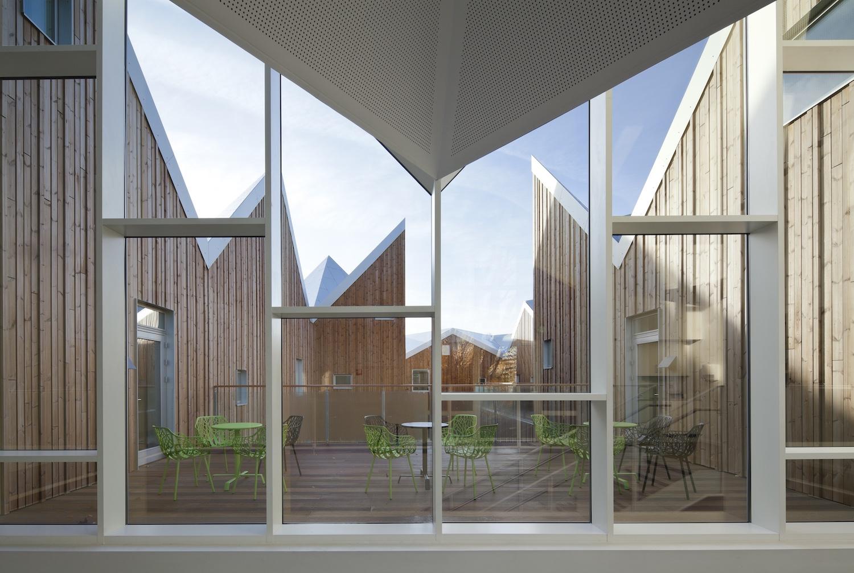 Et billede af et stort lyst glasparti, der fører ud til en altan indrettet med terrassemøbler