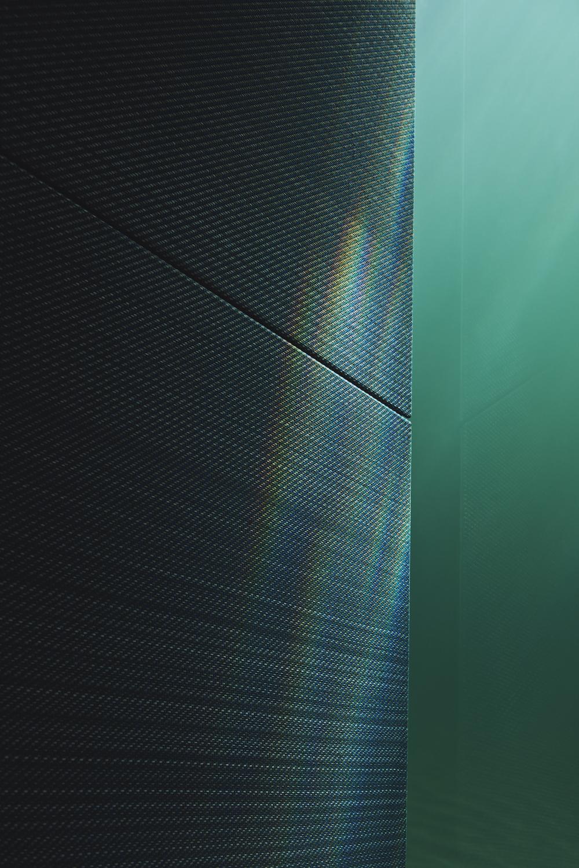 Et billede af et af de specialdesignede tekstilpaneler, der sikrer en god akustik i restauranten. Det er placeret direkte op mod glasruden, og det bliver tydeligt, at arkitekterne har arbejdet med kontraster.